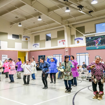 An Alaska Native dance ensemble performs inside a school gymnasium.