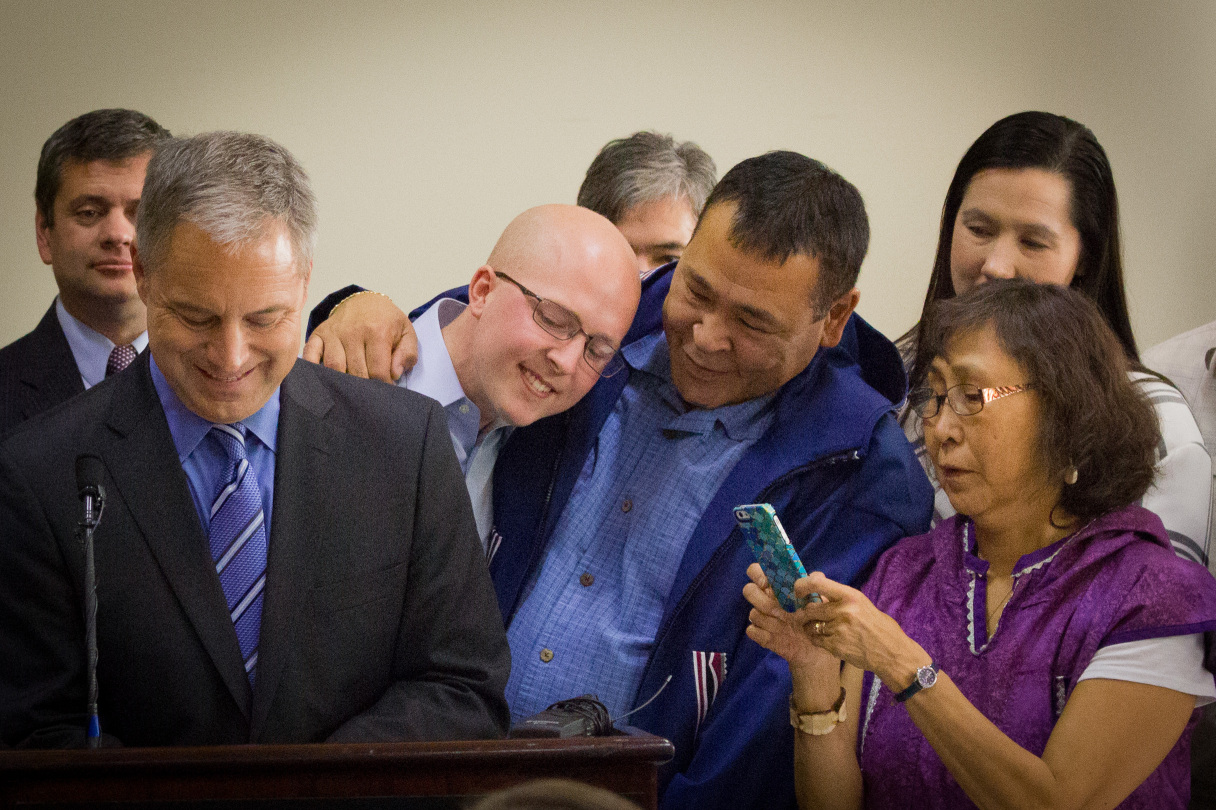 Representative Jonathan Kreiss-Tomkins of Sitka, Nome's Bernadette Yaayuk Alvanna-Stimpfle, and others look on as Gov. Sean Parnell signs the bill into law. Photo: Matthew F. Smith, KNOM.