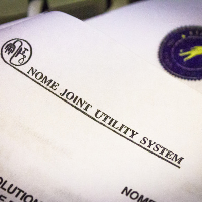 A close-up view of Nome Joint Utility System documents and letterhead.