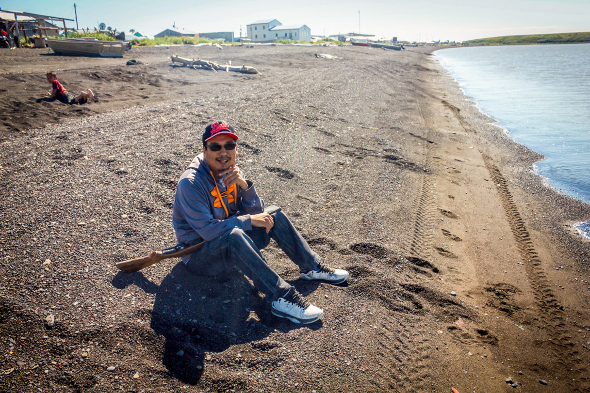 Summer in Stebbins, Alaska: resident Bernard Abouchuk sits on the beach in anticipation of a seal, which is hunted as a subsistence food. Photo: Emily Russell, KNOM.
