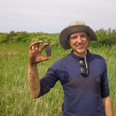 An archaeologist holds a large slate point in a grassy field