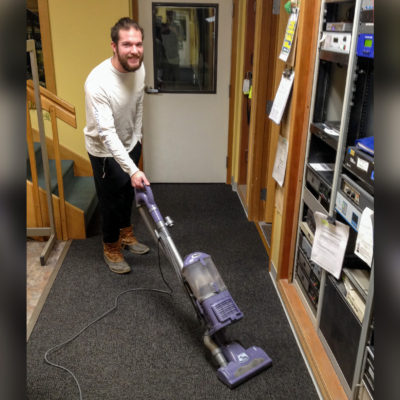 Davis Hovey uses a vacuum to clean the carpeting inside KNOM's radio studios.