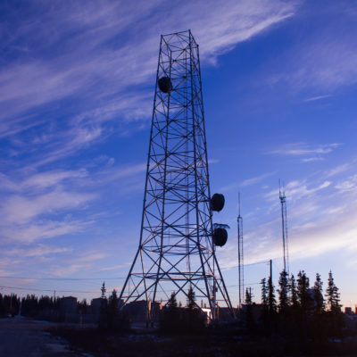 In Noorvik, the GCI tower juts up into the morning air. It is silhouetted against blue skies and partial clouds.