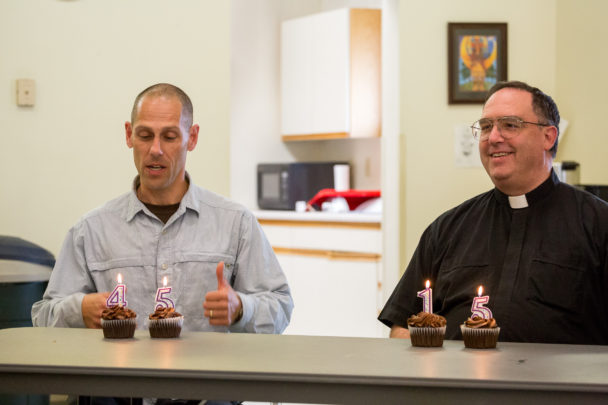 """On KNOM's 45th anniversary, and Father Ross Tozzi's 15th ordination anniversary, KNOM board president Paul Korchin and Father Ross Tozzi pose with cupcakes bearing birthday candles reading """"45"""" and """"15,"""" respectively."""