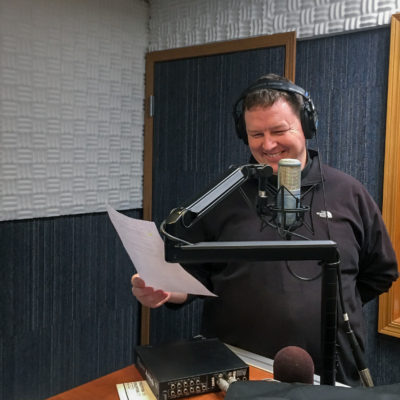 Father Jay Buhman at the microphone in KNOM's studios