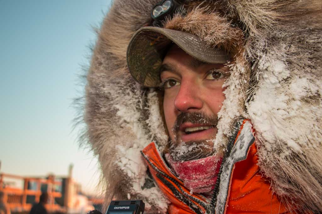 Pete Kaiser in an orange parka, moments after his 2017 Kuskokwim 300 victory