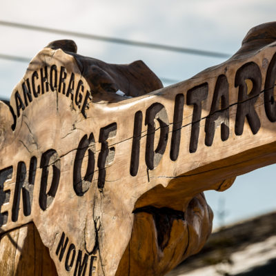 "Detail of the Iditarod finish line in Nome, called the Burled Arch. Text reads ""End of Iditarod,"" etched in wood."