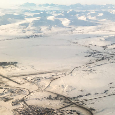 An aerial view of Nome, Alaska, its airport runways, and nearby mountains, covered in snow in late winter 2017.