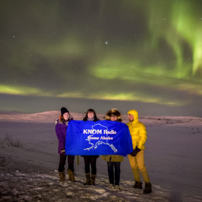 2016-2017 volunteers Karen Trop, Lauren Frost, Tyler Stup, and Davis Hovey hold a KNOM Radio banner under a particularly vivid, green-colored instance of the Northern lights near Nome.