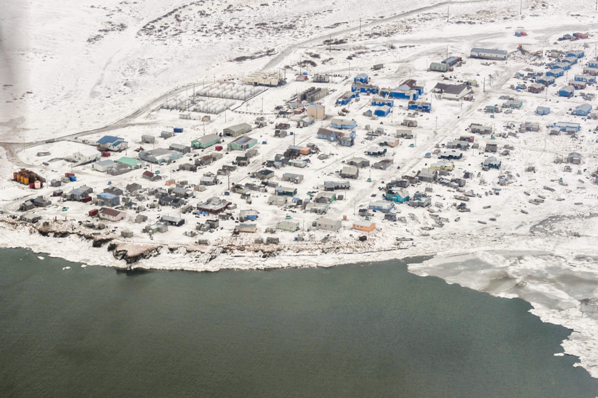 An aerial view over a snowy, coastal Alaska village in wintertime