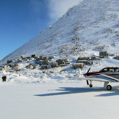 A landscape of Diomede, Alaska, in wintertime: a small airplane sits on a runway made of ice, with village houses nestled at the base of a steep hill in the background.