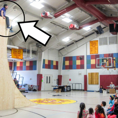 Nick Hanson, from the very top of a large, wooden structure, looks down on children sitting on the floor of the Kiana school gymnasium.