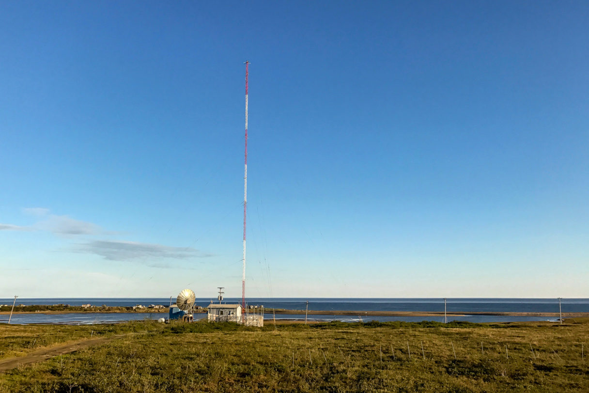 A radio station transmitter site on gently rolling tundra near the shoreline of the Bering Sea