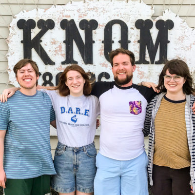 Tyler, Karen, Davis, and Lauren stand in front of the KNOM studio sign