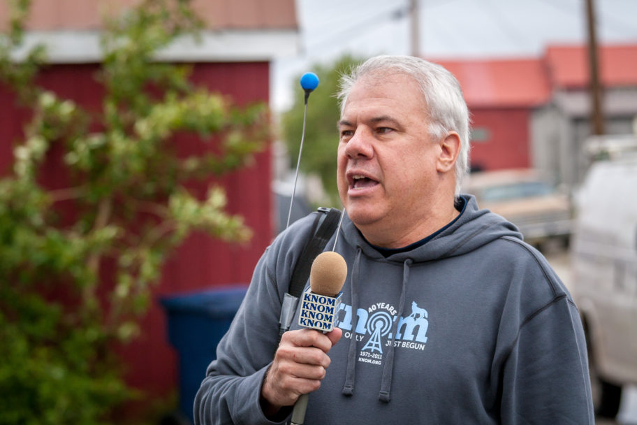 In a KNOM-branded sweatshirt, Ric talks into a KNOM microphone, standing outdoors.
