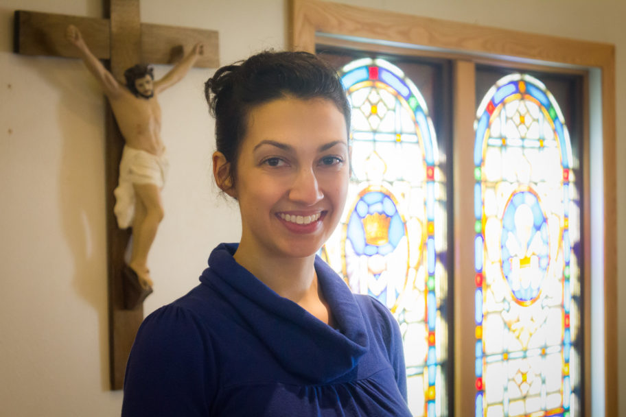 Margaret stands in front of stained glass windows and a crucifix inside Nome's St. Joseph Catholic Church.