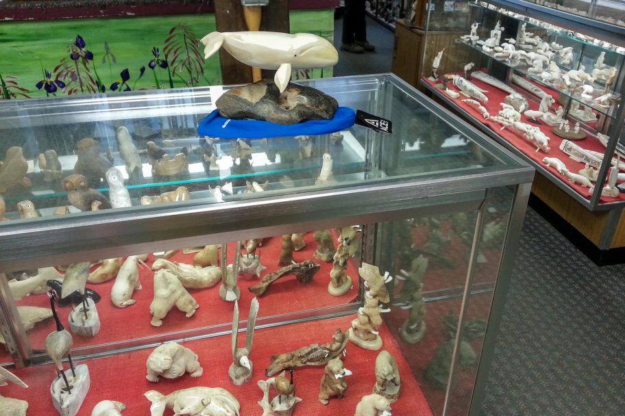Ivory carvings on display, behind glass, inside a small Nome gift shop.