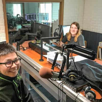 Nome youth Jonathan Outwater sits behind a radio microphone in the studio with KNOM volunteer Karen Trop.