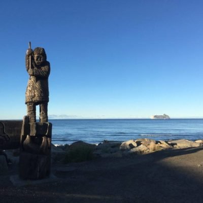 The cruise liner Crystal Serenity anchored offshore at Nome, with a Native statue in the foreground.