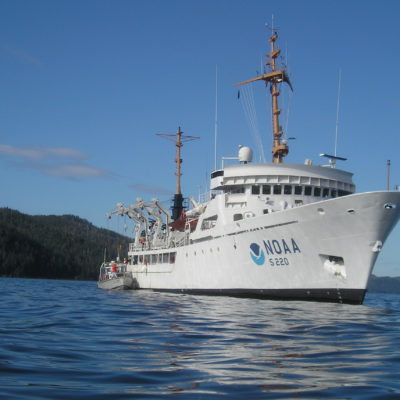 The NOAA Ship Fairweather with a forested coastline in the background.