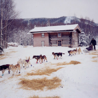 A dogsled team departs a log cabin at Slaven's Roadhouse. Photo Credit: National Park Service (2013)