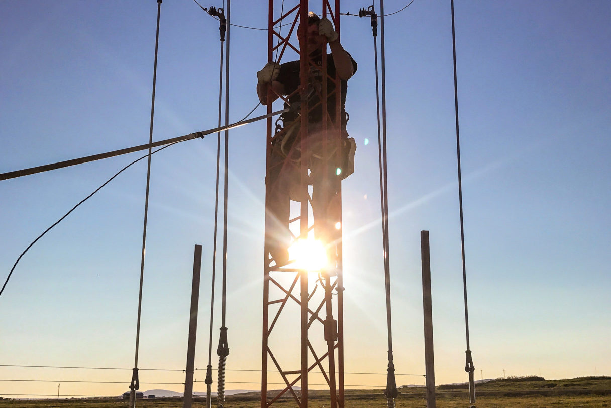 A silhouette of a crewman ascending a radio tower with the sun and tundra landscape behind him.