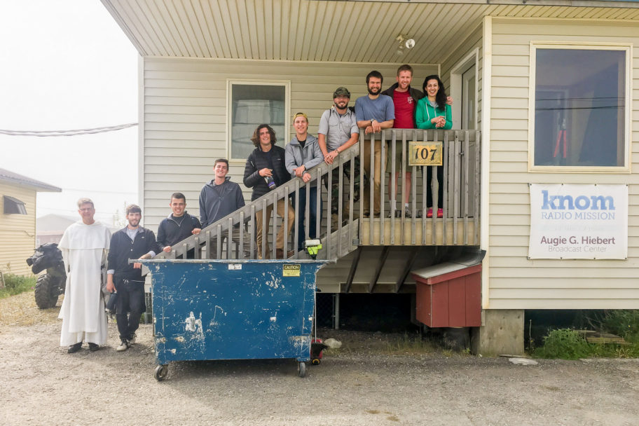 A smiling group of people lined up on KNOM Studios' front entrance steps.
