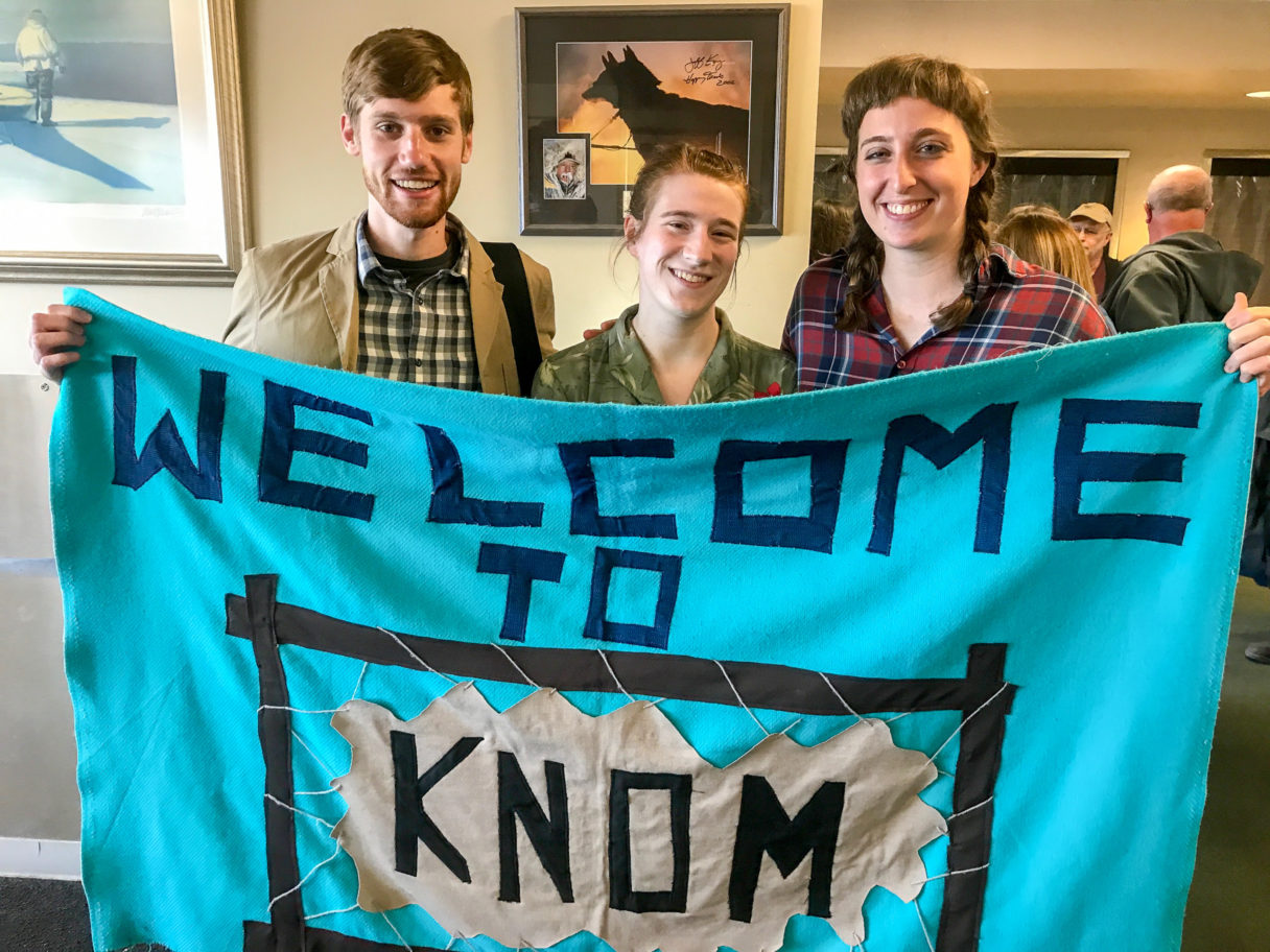 """At the Nome airport: Gabe Colombo, Karen Trop, and Zoe Grueskin holding the """"Welcome to KNOM"""" banner that greets newly-arriving volunteers."""