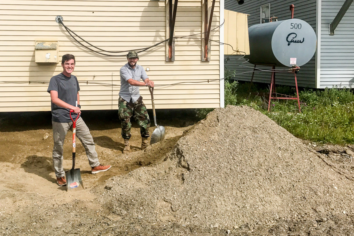 Two men with shovels stand aside a mound of dirt behind KNOM's garage