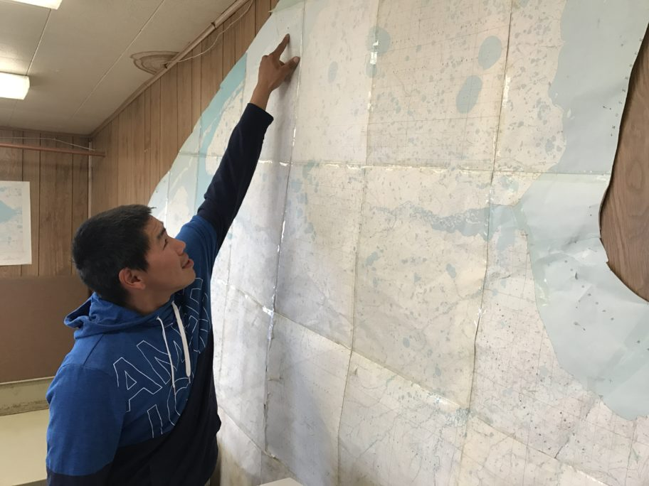 Corey Ningeulook points out where he hunts on gigantic map of Sarichef Island, taped to the wall of his office in Shishmaref. Photo: Grueskin/KNOM.