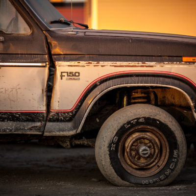 Side view of an old Ford pickup truck with rust marks and dust on its side.