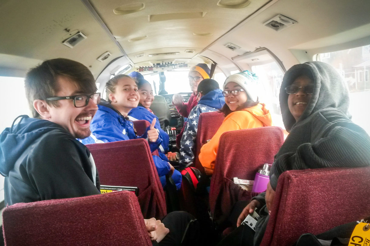 Teenage athletes inside a small airplane
