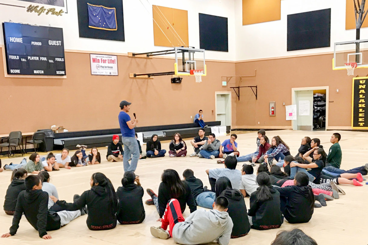 Teenagers sit in a large circle on the floor of a school gymnasium to listen to a presenter.