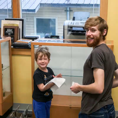 Young child and bearded man, both smiling, help dust display case in lobby of radio station