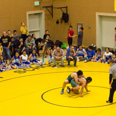 Wrestlers wrestle on a yellow mat surrounded by watching fans
