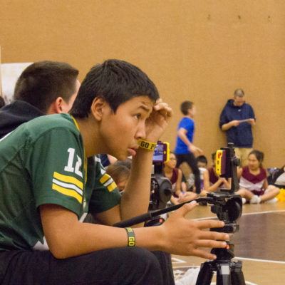 Student Broadcaster Mason Ivanoff lines up his shot at the Wrestling and Cheer Tournament in Unalakleet, AK.