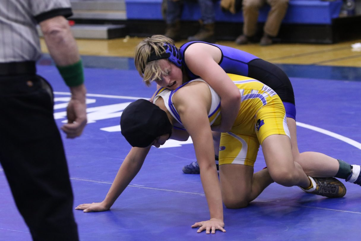 A referee stands in front of two young women in purple and yellow wrestling on a purple mat