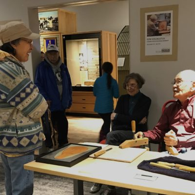 """Artist Ron Senungetuk speaks with visitors to the Carrie M. McLain Memorial Museum. His work is featured in a special exhibit """"Carving a Path of Cultural Continuity."""""""