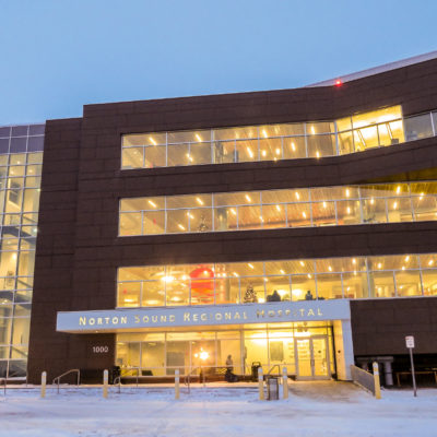 The Nome hospital at dusk, viewed from the front, with light streaming through its windows.