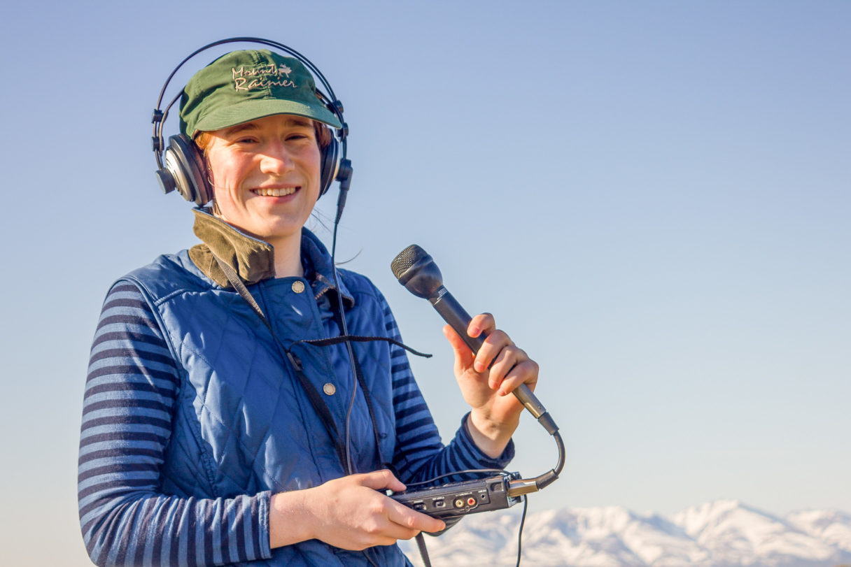 KNOM's Karen Trop, in a blue long-sleeve t-shirt and vest, holds a microphone and small audio recorder, smiling at the camera.