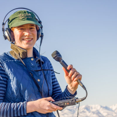 Volunteer Karen Trop, in a blue long-sleeve t-shirt and vest, holds a microphone and small audio recorder, smiling at the camera.