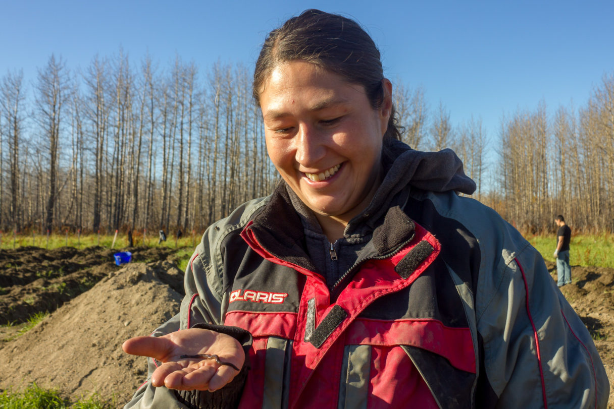 Farm manager smiles at an earthworm in her hand.