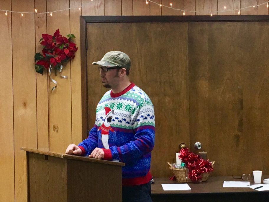 Sporting a jolly Christmas sweater with a shark on it, Colby Engstrom tells the Nome Port Commission his desired location for Sea Laundry lacks a water and sewer line.