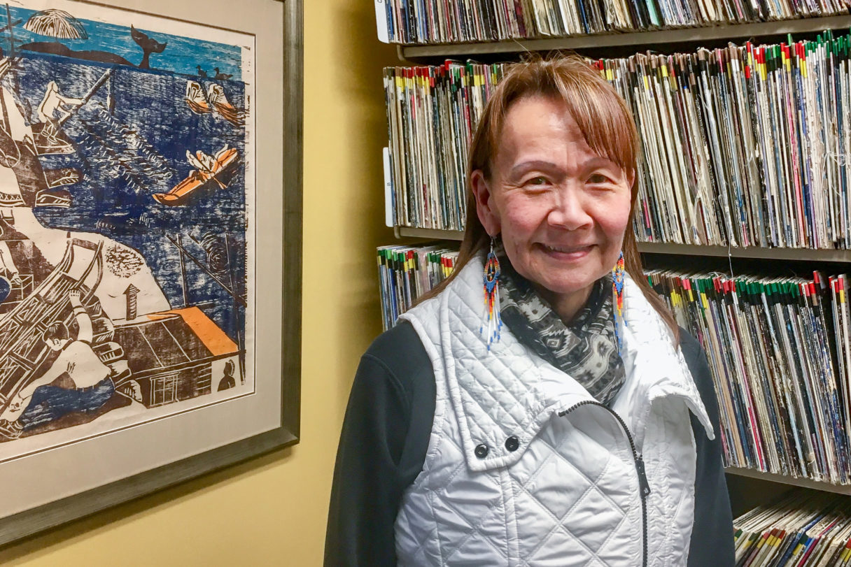 Woman in white vest stands next to Alaska Native painting and shelves of vinyl records.