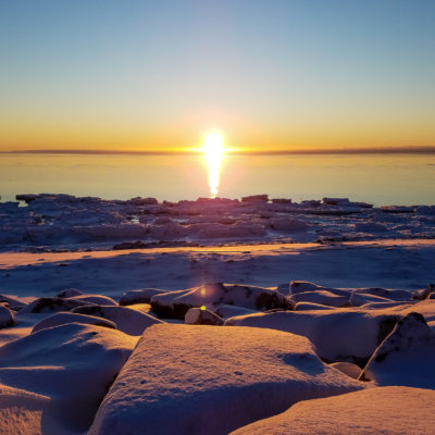 Sunset over the snow and ice of Nome's winter shoreline.