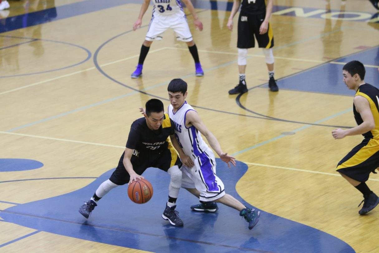 A Unalakleet boy, dressed in black and yellow, dribbles the ball and is blocked by a Nome boy, dressed in white and purple