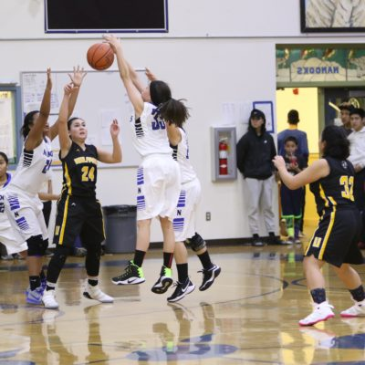 Nome girls, in white, fight with Unalakleet girls, in brown, fight to recover the basketball