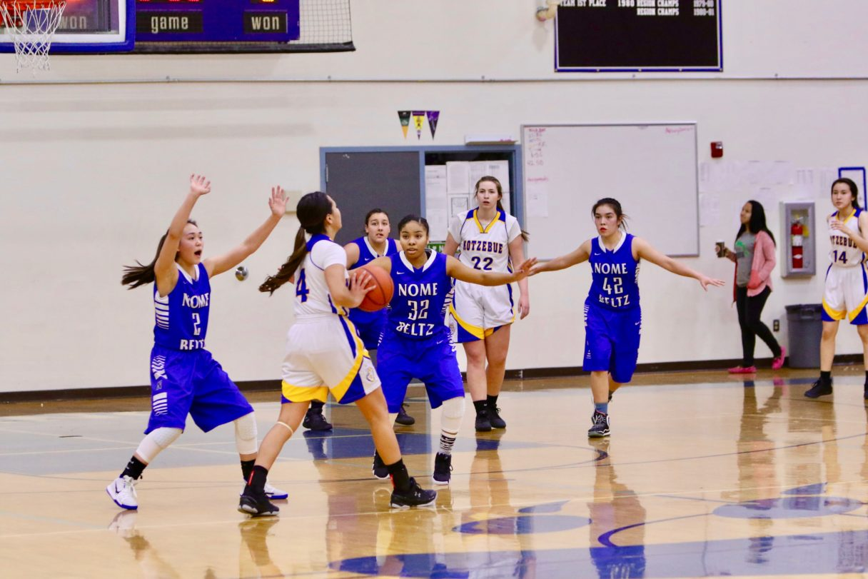 Three Nome girls, in purple, block a Kotzebue girl, in white, who tries to pass the ball