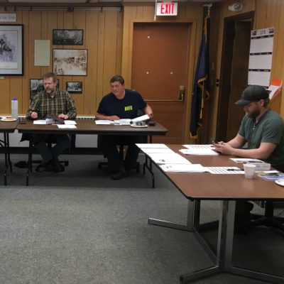 Commissioners Scot Henderson and Shane Smithhisler and Harbormaster Lucas Stotts review documents at a meeting of the Nome Port Commission in Feb. 2018.