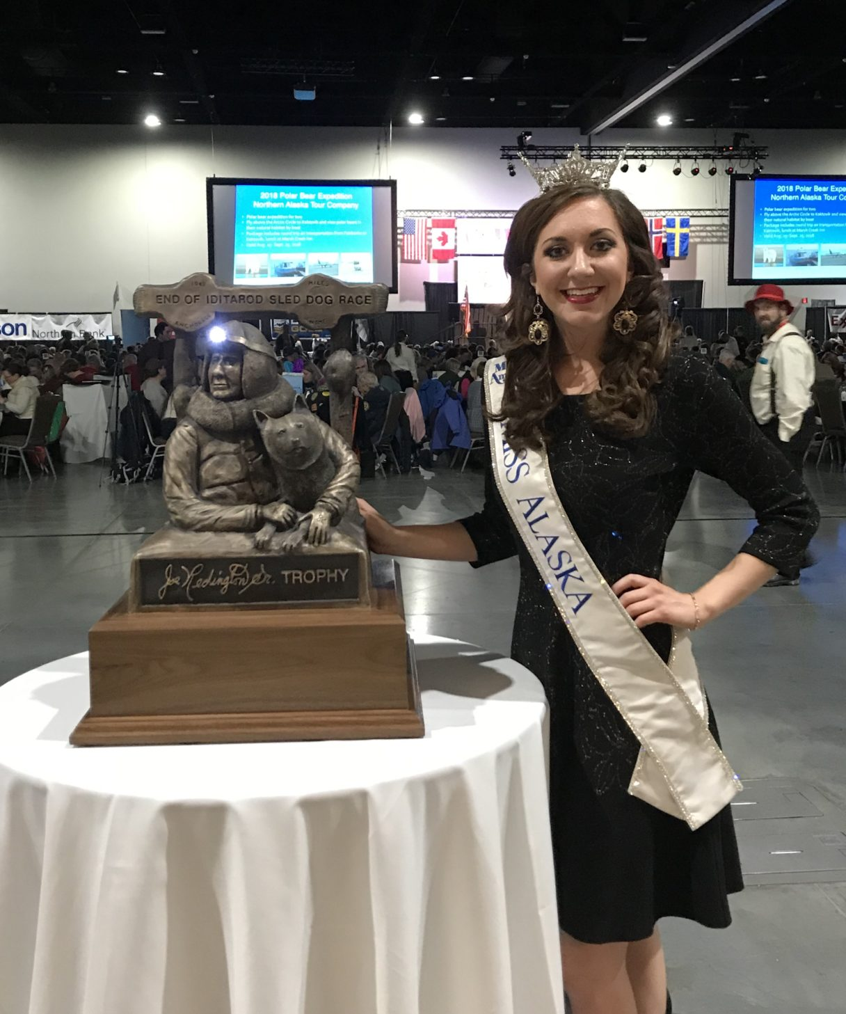 Miss Alaska 2017, Angelina Klapperich, poses next to the trophy (bearing a likeness of the late Joe Redington, Sr.) that will be given to the 2018 Iditarod champion.
